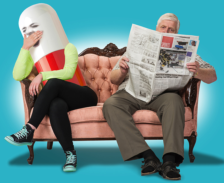 Elderly man sitting on couch, reading newspaper, ignores yawning pill sitting beside him.